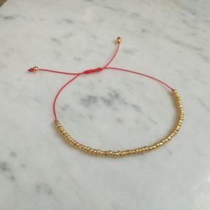 Pulsera hilo rojo mostacillas doradas